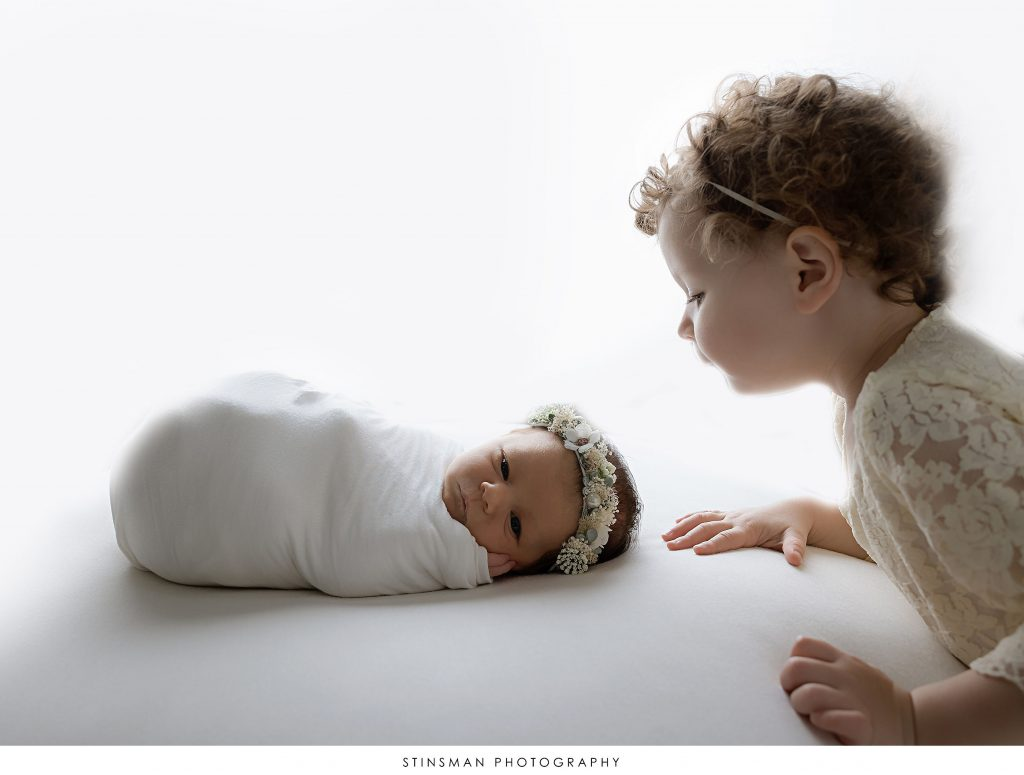 Newborn baby girl awake and her sister looking at her at her newborn photoshoot