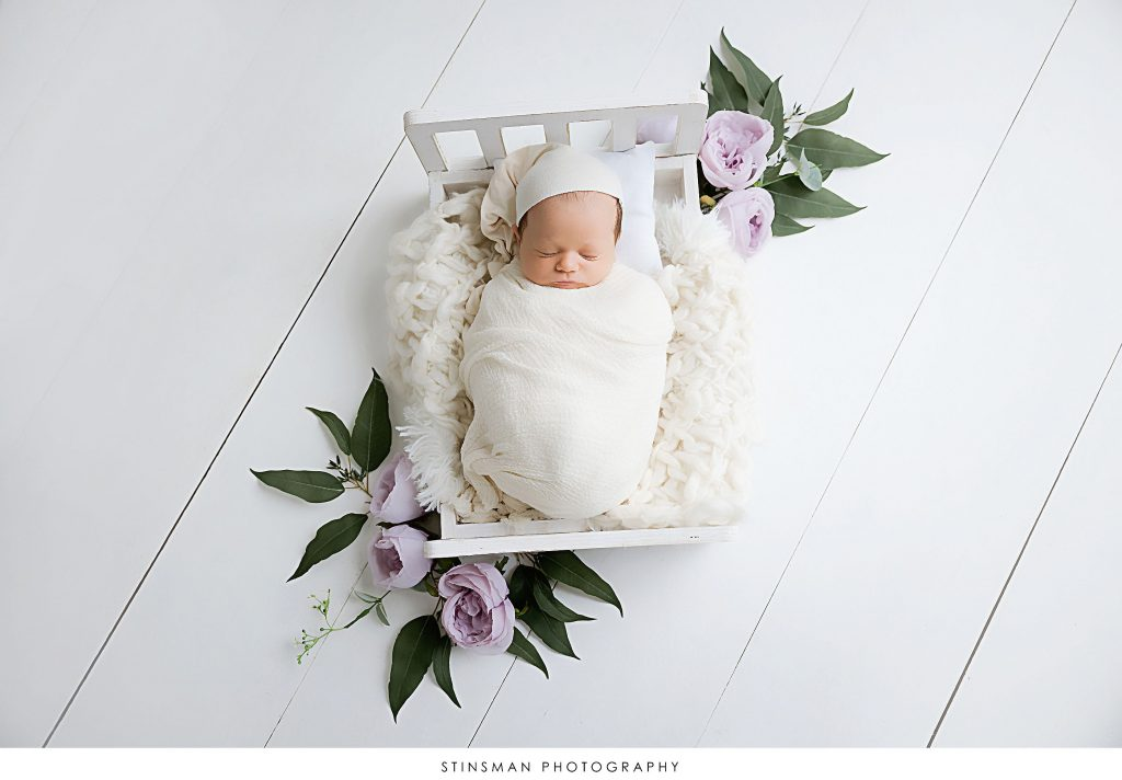 Newborn baby girl posed in a bedtime set at her newborn photoshoot