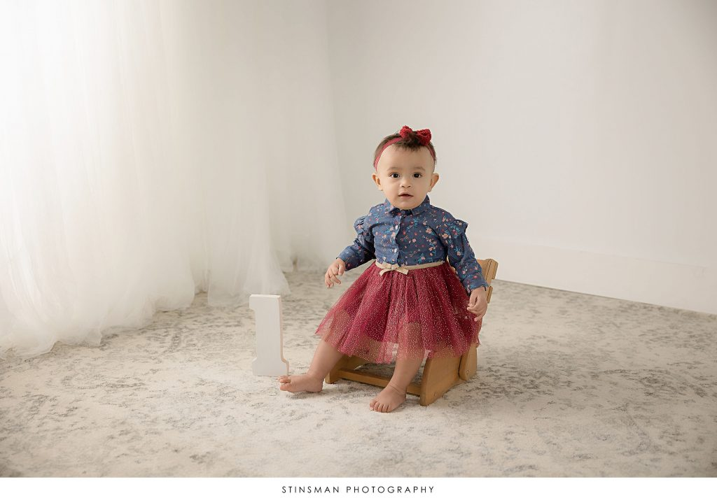 Baby girl posing at her one year old milestone photoshoot