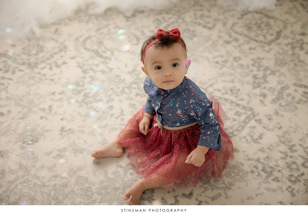 Baby girl posing for her first birthday milestone session