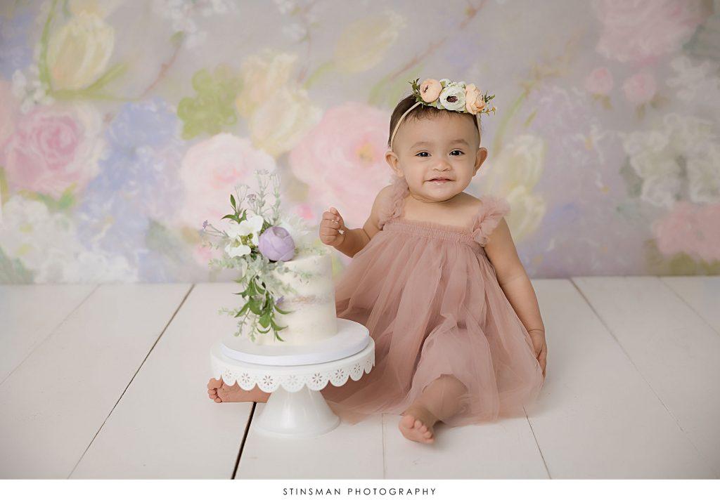 Baby girl smiling during her cake smash at her milestone photoshoot
