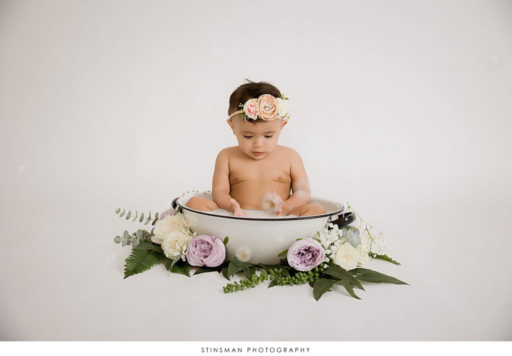 Baby girl playing in her milk bath at her first birthday milestone photoshoot