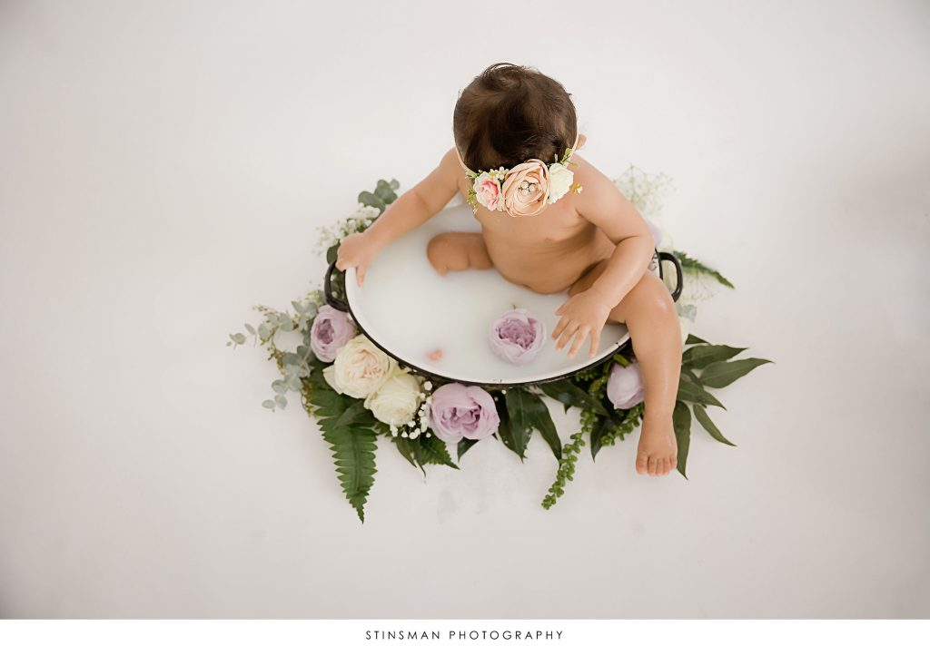 Baby girl looking at a purple flower at her milestone photoshoot