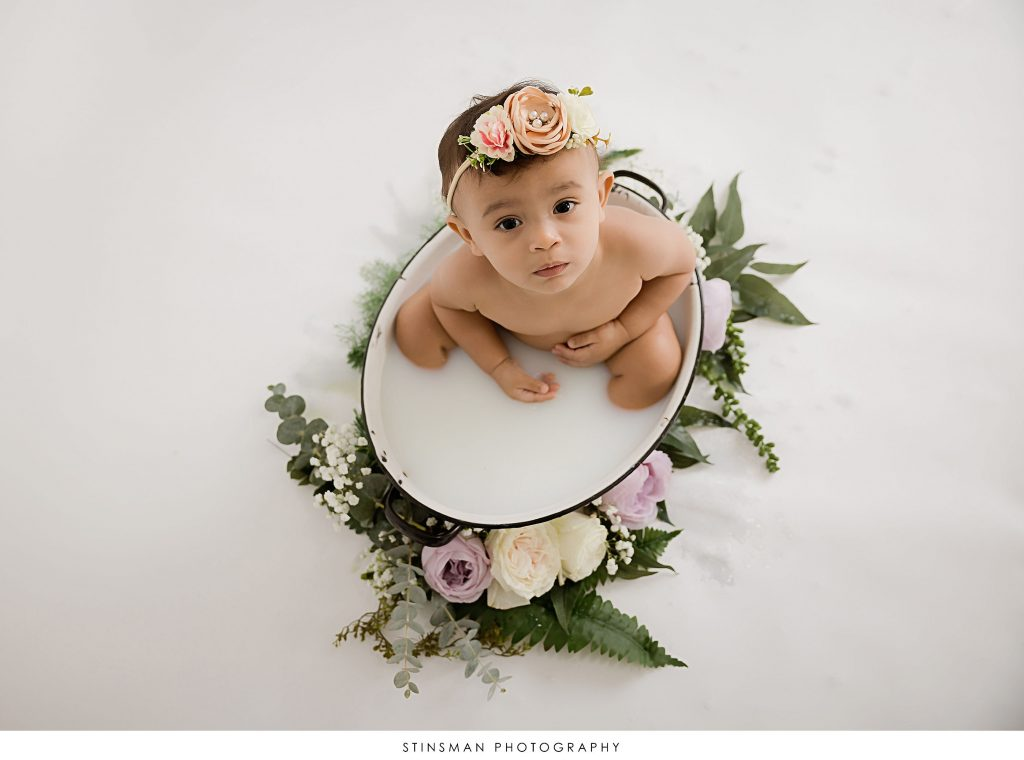 Baby girl sitting in a milk bath at her first birthday milestone photoshoot