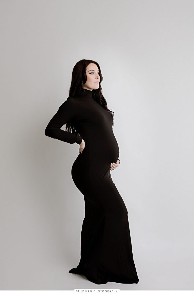 Pregnant mom in a formal black dress posing at her maternity photoshoot