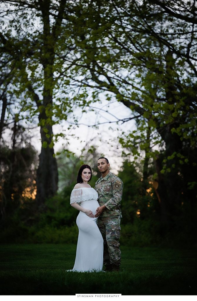 Pregnant mom and dad posing outside at their maternity photoshoot