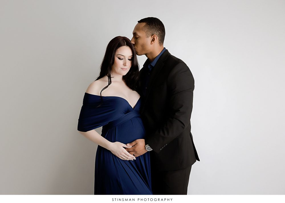 Pregnant mom and dad posing in formal wear at their maternity photoshoot