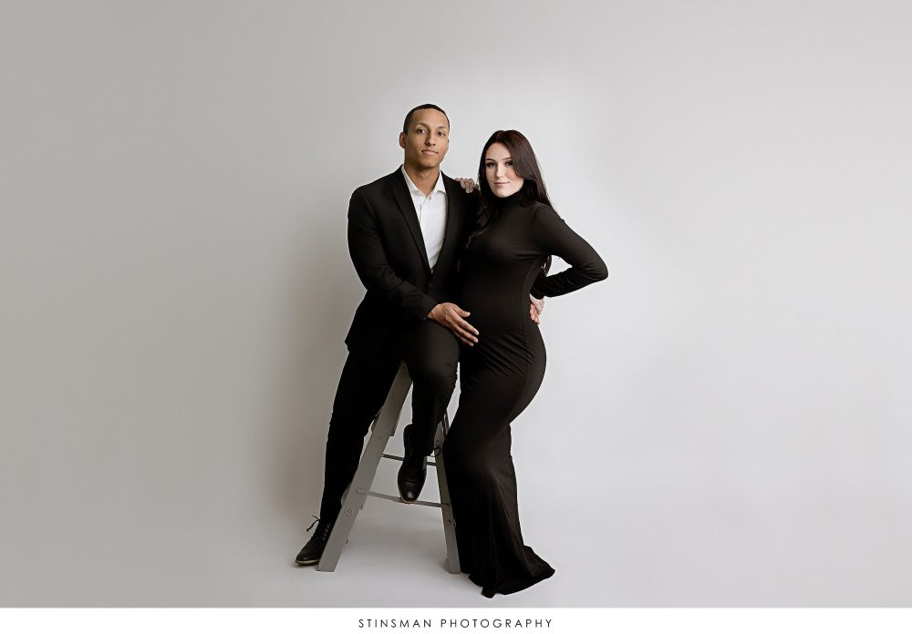 Pregnant mom and dad posing at in black formal outfits at their maternity photoshoot