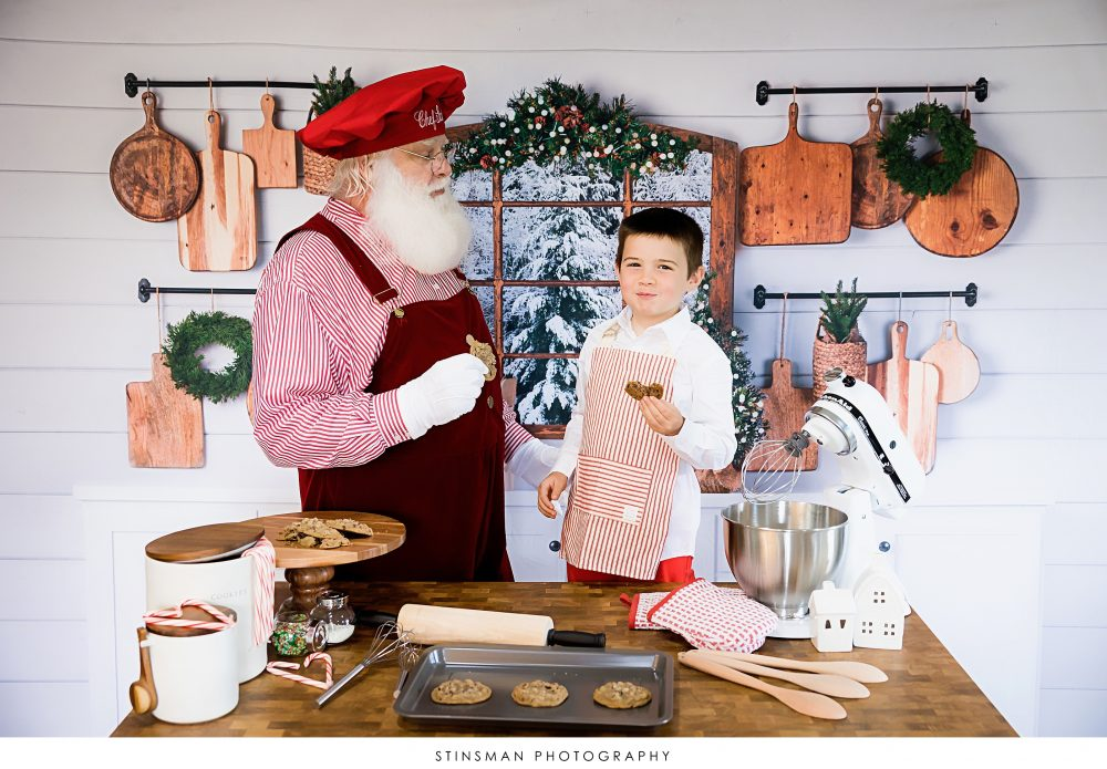 little boy eating a cookie with santa