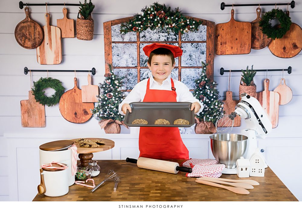 5 year old boy showing off his cookies in photo shoot