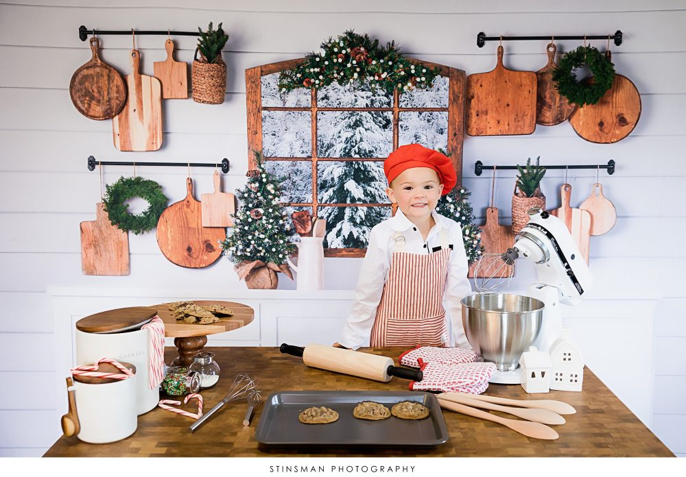 little boy wearing a red hat in holiday photo set