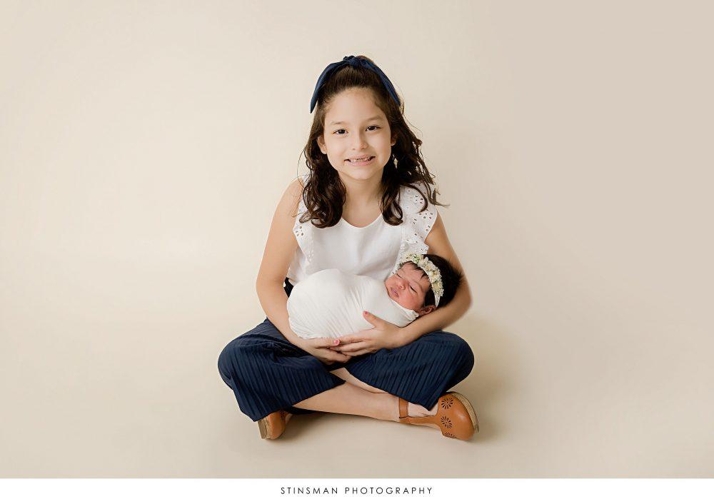 Newborn baby girl and big sister posed at her newborn photoshoot