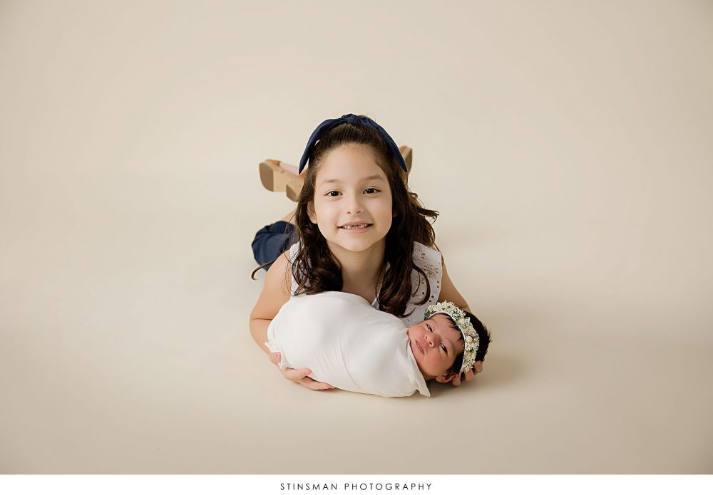 Newborn baby girl and her sister posed at her newborn photoshoot