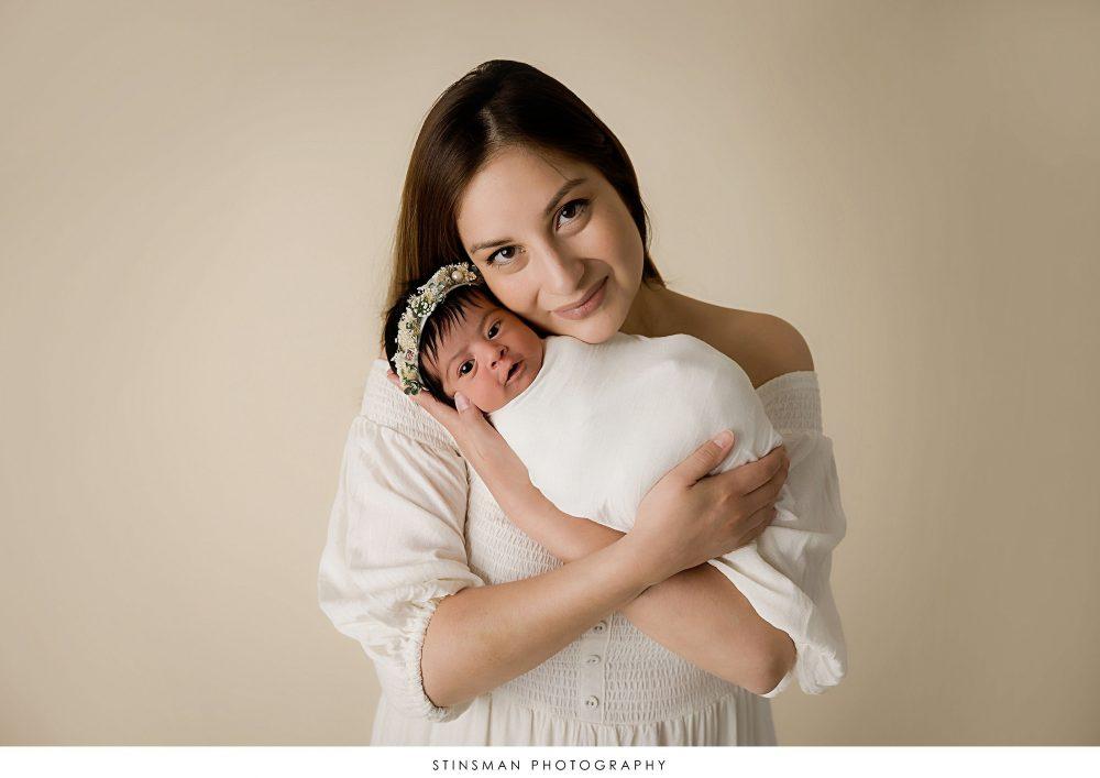 Mom posed with newborn baby girl at their newborn photoshoot