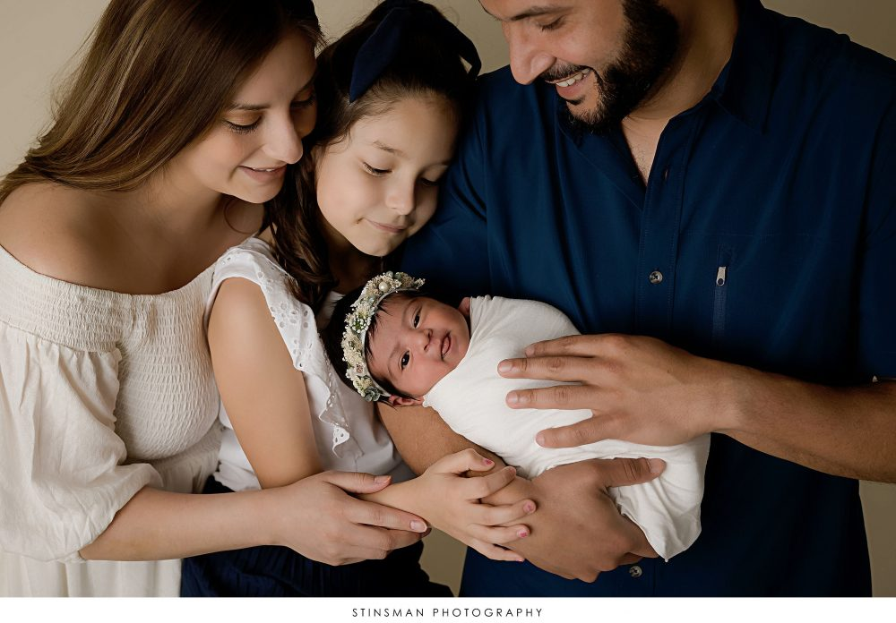 Parents and big sister looking at newborn baby girl at her newborn photoshoot