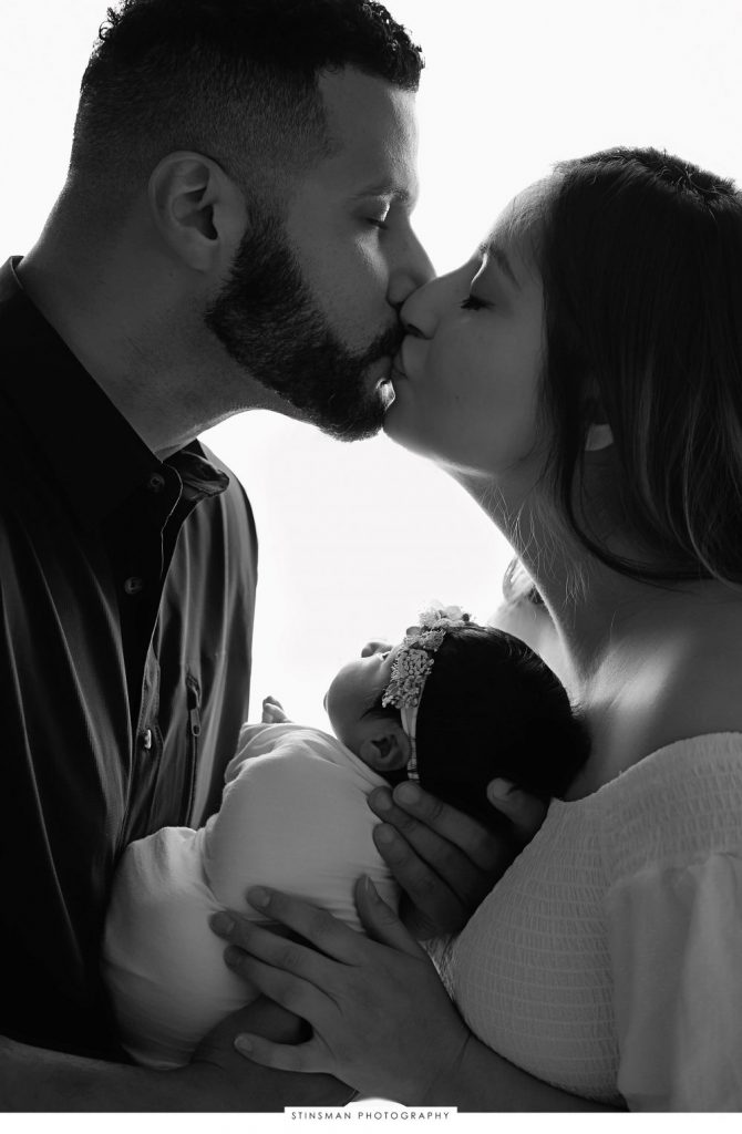 Parents kissing and holding their newborn baby girl at their newborn photoshoot
