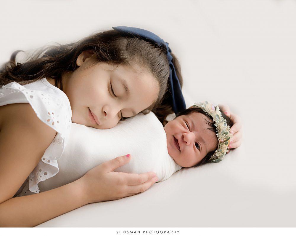 Newborn baby girl smirking while her big sister snuggles at her newborn photoshoot