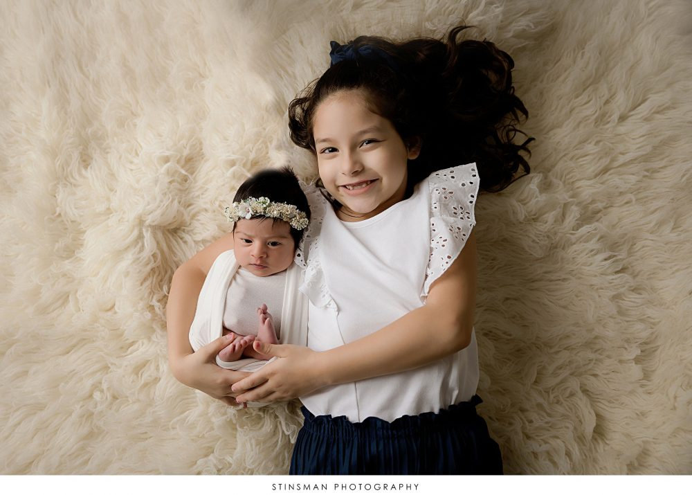 Newborn baby girl posed with her big sister a her newborn photoshoot