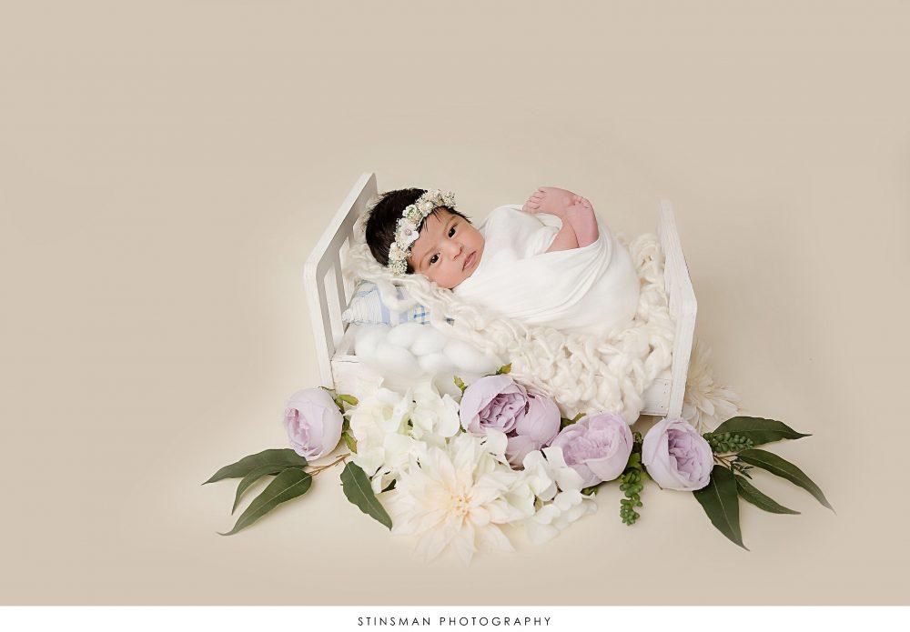 Newborn baby girl posed at her newborn photoshoot