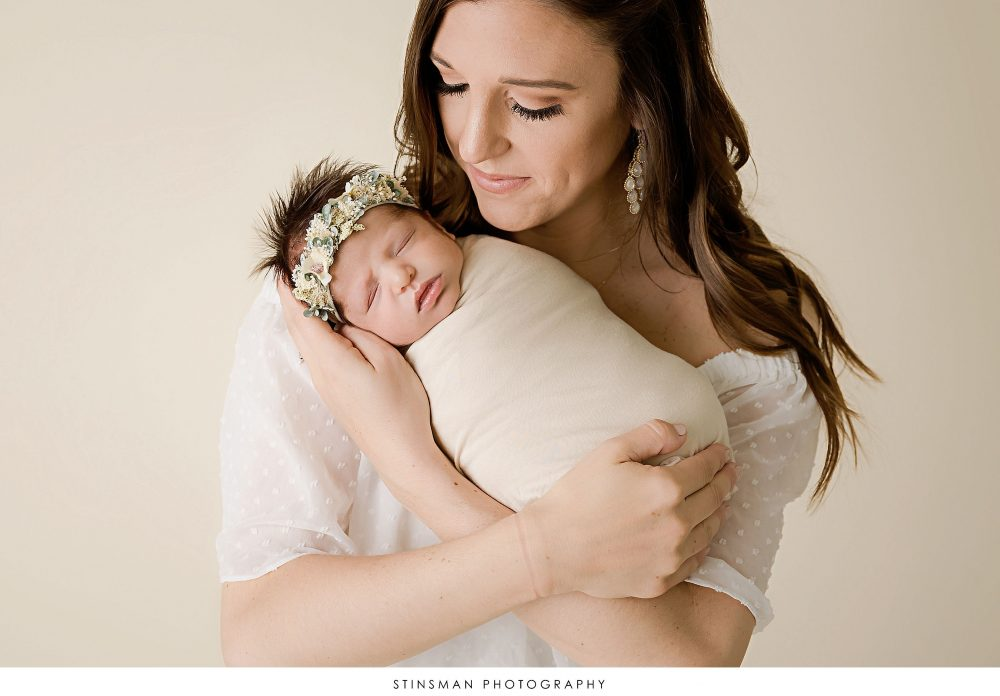 mom snuggling her baby girl at their newborn photoshoot