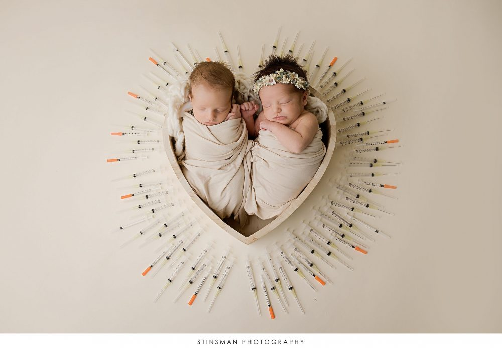 Newborn twins posed with IVF needles at newborn photoshoot