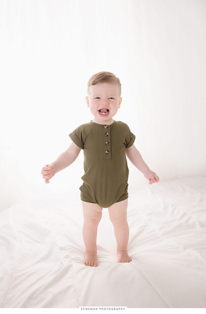 One year old little boy smiling at his milestone photoshoot