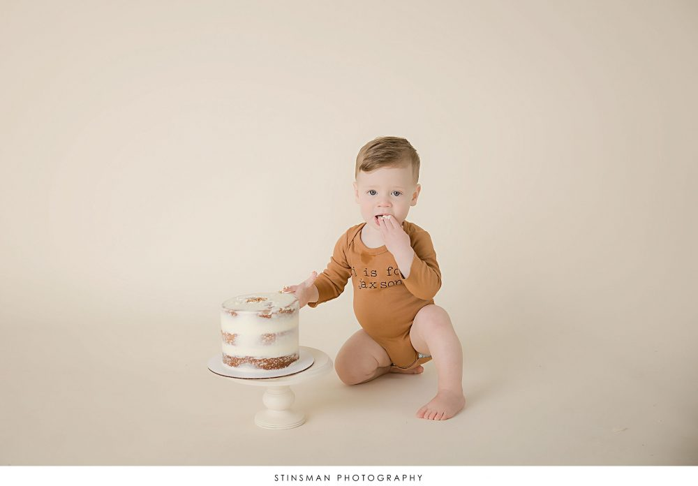 One year old boy eating his cake at his milestone photoshoot