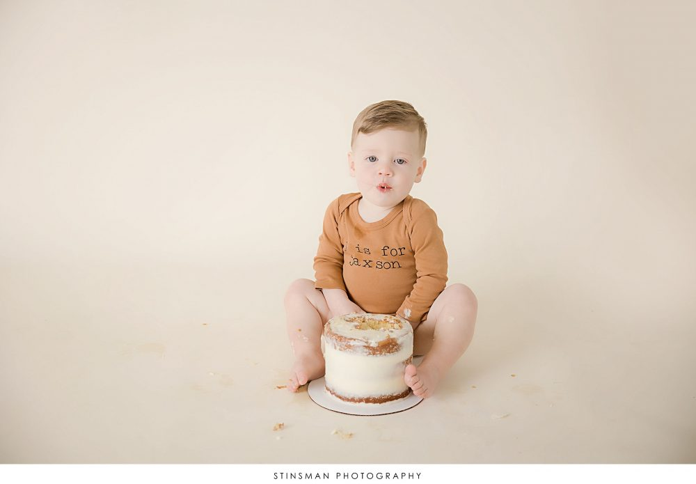 One year old boy tasting his cake at his milestone photoshoot