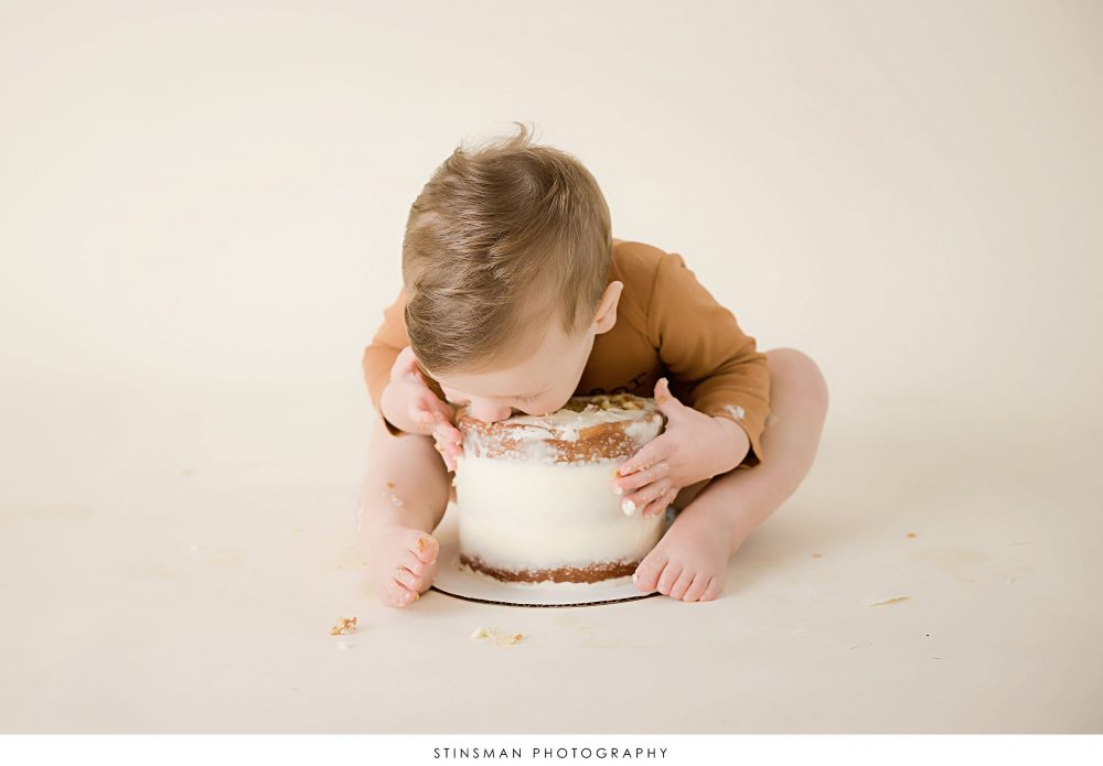 One year old little boy tasting his cake at his milestone photoshoot