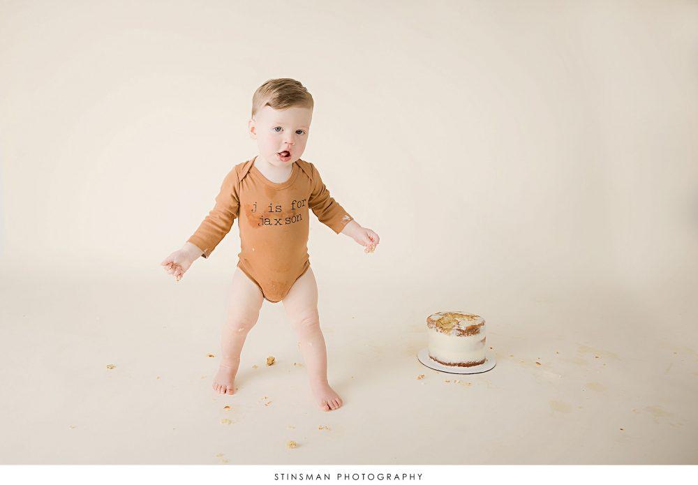One year old boy walking near his cake at his milestone photoshoot
