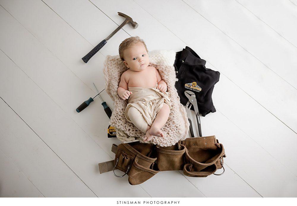 Newborn baby boy posed at his newborn photoshoot.