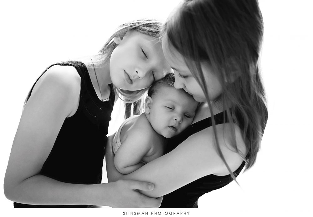 Newborn baby boy posed with his sisters at his newborn photoshoot