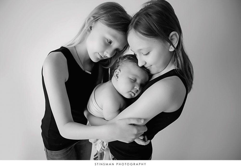 Newborn baby boy and his sisters posing at his newborn photoshoo
